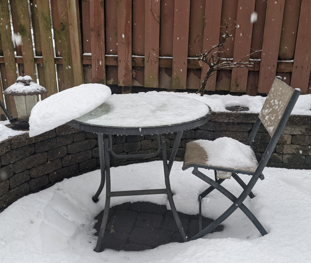 Snow Precariously Balanced on Patio Table